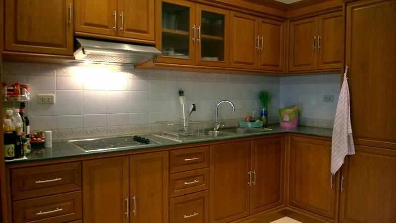 La cuisine à l'occidentale, encastrée, équipée d'un plan de travail en granite, un réfrigérateur, un congélateur, des plaques de cuisson vitrocéramique et un système de ventilation.